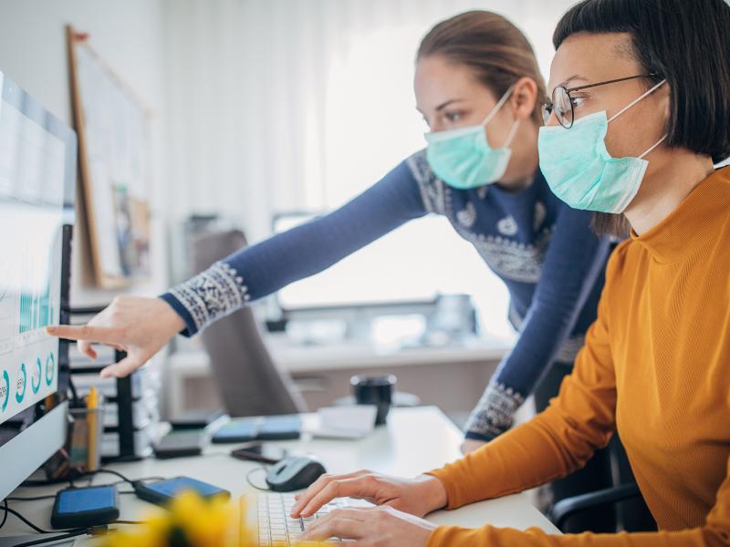 Mitarbeiter des Gesundheitsamt schauen auf einen Monitor