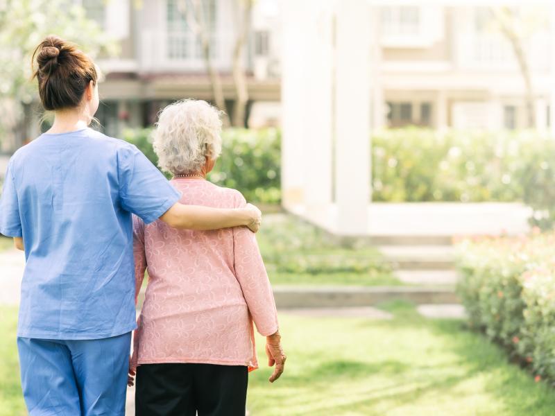 Altenpflegerin und Seniorin gehen zusammen spazieren.